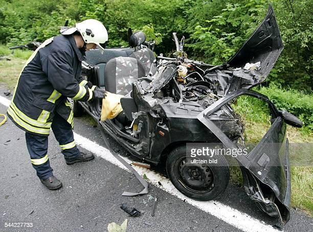 Deutschland MecklenburgVorpommern Ralswiek Ein Feuerwehrmann schneidet das Wrack des verunglueckten Renault Clio auf der Bundestrasse B 96 bei...