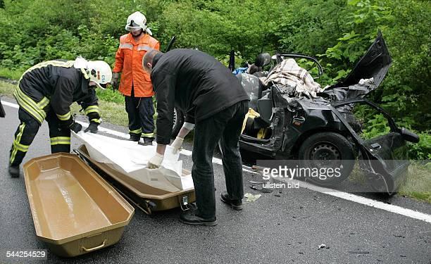 Deutschland MecklenburgVorpommern Ralswiek Ein Feuerwehrmann und ein Bestattungsmitarbeiter bergen die Toten aus dem Wrack des verunglueckten Renault...