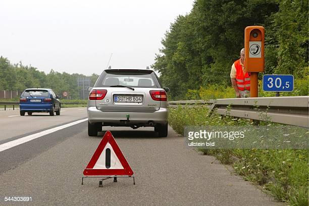 Deutschland Strassenverkehr Pannenfahrzeug an einer Notrufsäule auf dem Standstreifen der Autobahn Der Fahrer trägt eine orange Sicherheitsweste und...