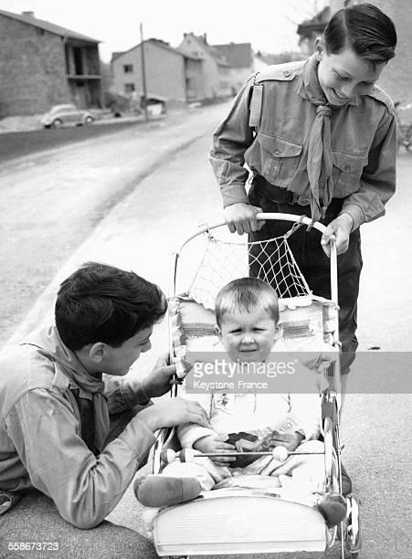 Deux boy scouts s'occupent d'un jeune enfant en poussette en l'absence de sa mère le 25 avril 1962 à Munich Allemagne