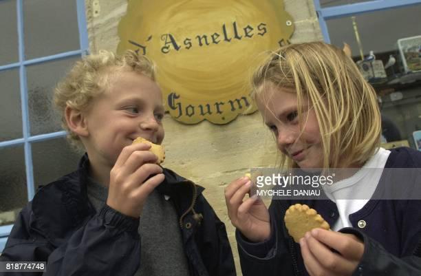 Deux enfants Camille et Ludovic goûtent des biscuits d'Antoine Cormier devant sa boutique le 10 juillet 2001 à Asnelles Antoine Cormier ancien...