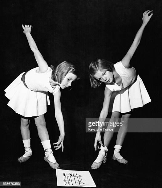 Deux enfants danseuses répètent une chorégraphie en s'inspirant d'une série de symboles sur une feuille au sol leur indiquant les positions à...