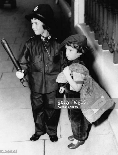 Deux enfants déguisés en gendarme et en voleur photographiés à leur arrivée au Hyde Park Hotel où se déroule une fête de charité pour les enfants à...