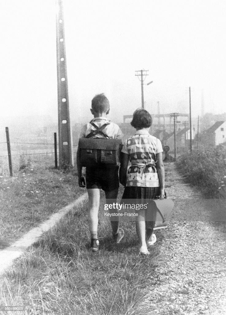 Deux enfants portent leurs cartables sur le chemin de l'école.