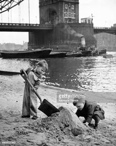 Deux garçons font un château de sable sur les quais de Londres RoyaumeUni le 5 mai 1952