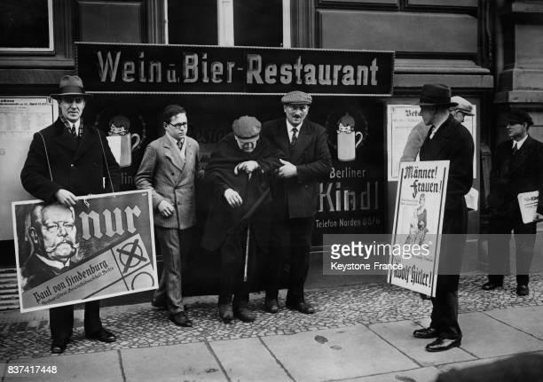 Deux groupes politiques opposés soutenant d'une part Hindenburg d'autre part Hitler poursuivent de leurs assiduités un vieil homme à la sortie d'un...