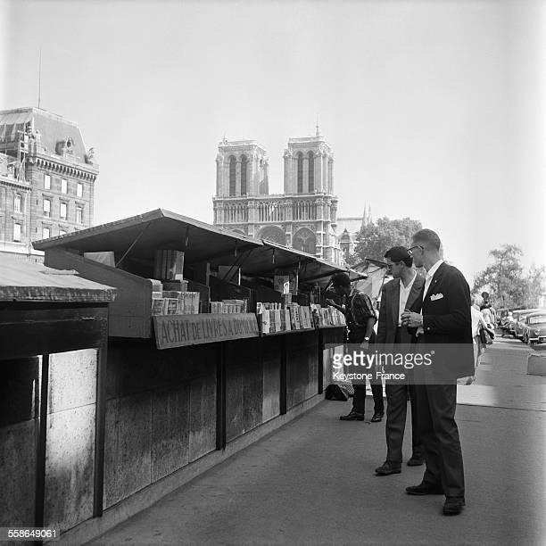 Deux hommes regardant chez un bouquiniste des quais de Seine les livres anciens dans les caisses ouvertes sur le parapet la cathédrale NotreDame en...