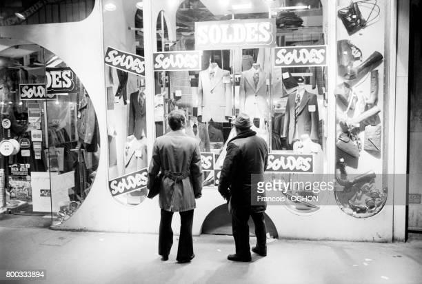 Deux hommes regardent la vitrine d'un magasin d'habillement en période de soldes en février 1976 à Paris France