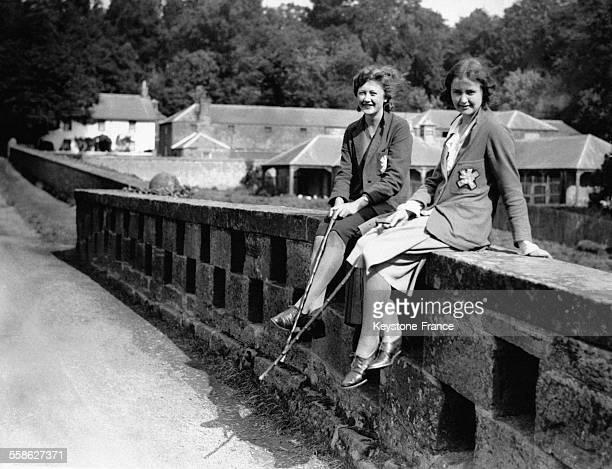 Deux jeunes femmes assises sur un petit muret regardent le château de Glamis Ecosse RoyaumeUni le 21 août 1930