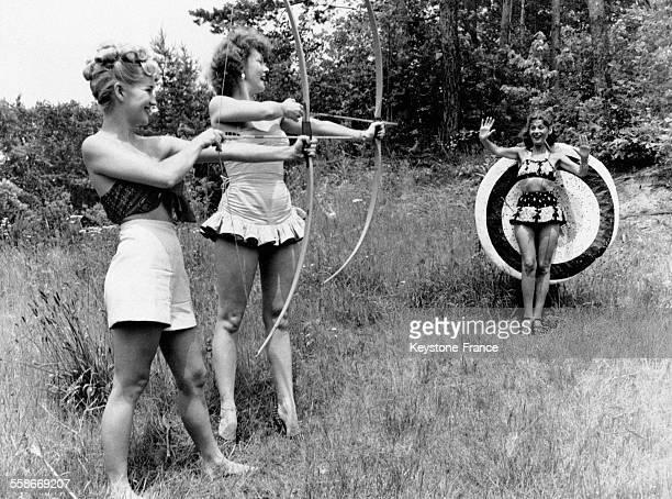 Deux jeunes femmes munies chacune d'un arc s'apprêtent à tirer une flèche sur une cible devant laquelle se tient une troisième jeune femme