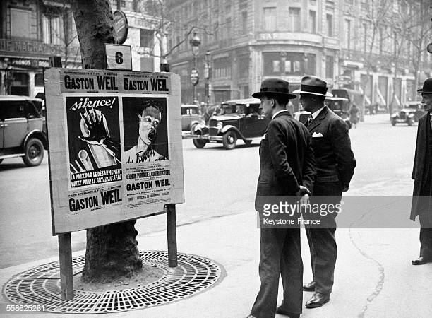 Deux jeunes électeurs parisiens contemplent l'affiche du candidat socialiste SFIO représentant un bras humain imposant le silence aux canons prêts à...