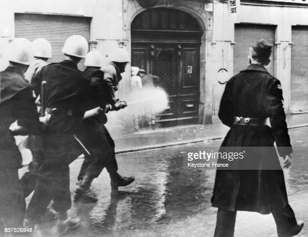 Deux manifestants en faveur de l'annexion de Triestre à la Yougoslavie coincés dans une porte cochère ne peuvent pas échapper à la douche froide que...
