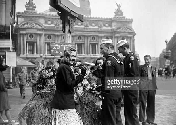 Deux marins offrent un bouquet de muguet à une jeune femme devant l'Opéra Garnier à Paris France le 1er mai 1945