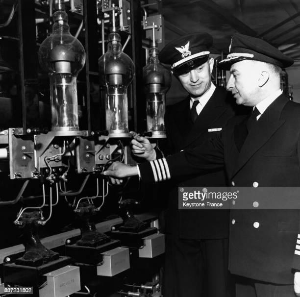 Deux officiers américains à bord du 'USS Courier' règlent l'émetteur principal permettant de diffuser 'Voice of America' audelà du Rideau de Fer le...