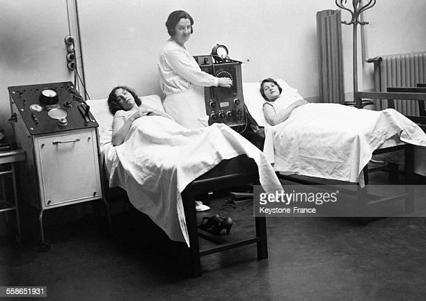 Deux Parisiennes allongées sur des lits pour un examen médical gratuit à l'Institut à Paris France le 21 juillet 1930