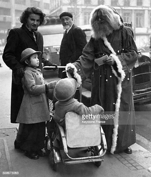 Deux petites filles en poussette ont rencontré le Père Noël sur le trottoir devant les grands magasins circa 1940 à Paris France