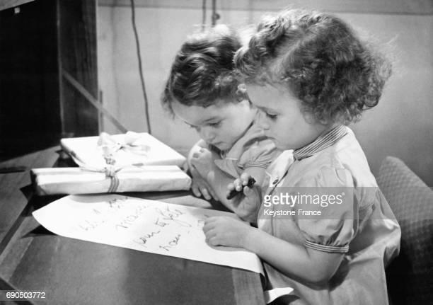 Deux petits enfants écrivent un mot tendre qu'ils offriront à leur maman pour sa fête à Paris France le 29 mai 1958