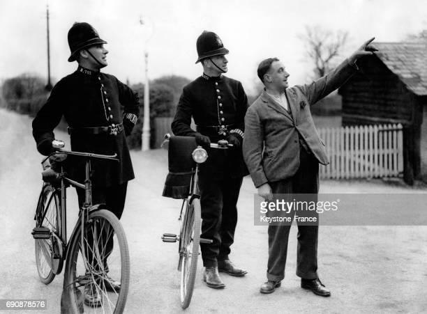 Deux policiers à vélo interrogent un homme sur l'évasion de plusieurs patients d'un asile psychiatrique dans la campagne environnant la ville le 2...