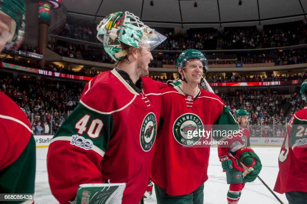 Devan Dubnyk and Eric Staal of the Minnesota Wild celebrate after defeating the Carolina Hurricanes on April 4 2017 at the Xcel Energy Center in St...