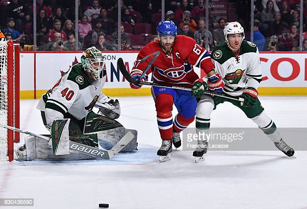 Devan Dubnyk and Jared Spurgeon of the Minnesota Wild defend the goal against Max Pacioretty of the Montreal Canadiens in the NHL game at the Bell...