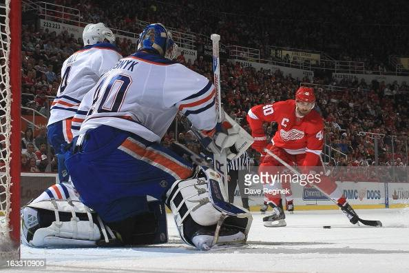 Devan Dubnyk and Taylor Hall of the Edmonton Oilers defend the net as Henrik Zetterberg of the Detroit Red Wings takes a shot during a NHL game at...