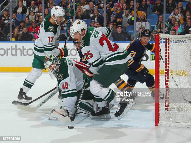 Devan Dubnyk Jonas Brodin and Marcus Foligno of the Minnesota Wild look to cover the puck as Kyle Okposo the Buffalo Sabres skates by during an NHL...