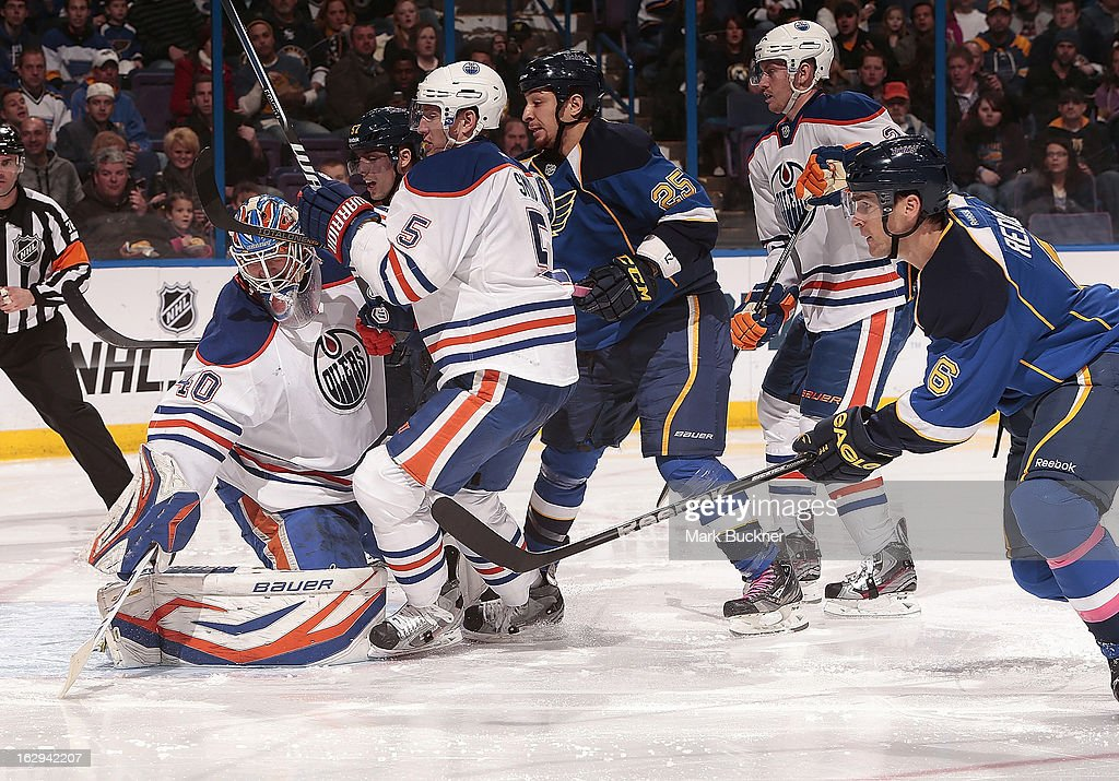 <a gi-track='captionPersonalityLinkClicked' href=/galleries/search?phrase=Devan+Dubnyk&family=editorial&specificpeople=2089794 ng-click='$event.stopPropagation()'>Devan Dubnyk</a> #40 of the Edmonton Oilers looks for the puck as he is run into by several players in an NHL game against the St. Louis Blues on March 1, 2013 at Scottrade Center in St. Louis, Missouri.