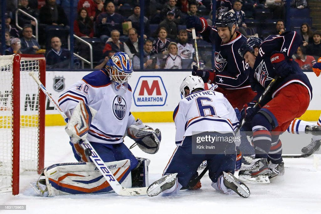 Devan Dubnyk #40 of the Edmonton Oilers makes a save as Ryan Whitney #6 of the Edmonton Oilers attempts to keep R.J. Umberger #18 of the Columbus Blue Jackets and Derek Dorsett #15 of the Columbus Blue Jackets from getting to the rebound on March 5, 2013 at Nationwide Arena in Columbus, Ohio.