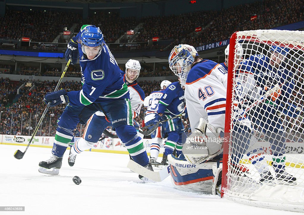 Devan Dubnyk of the Edmonton Oilers makes a save on David Booth of the Vancouver Canucks during their NHL game at Rogers Arena December 13 2013 in...