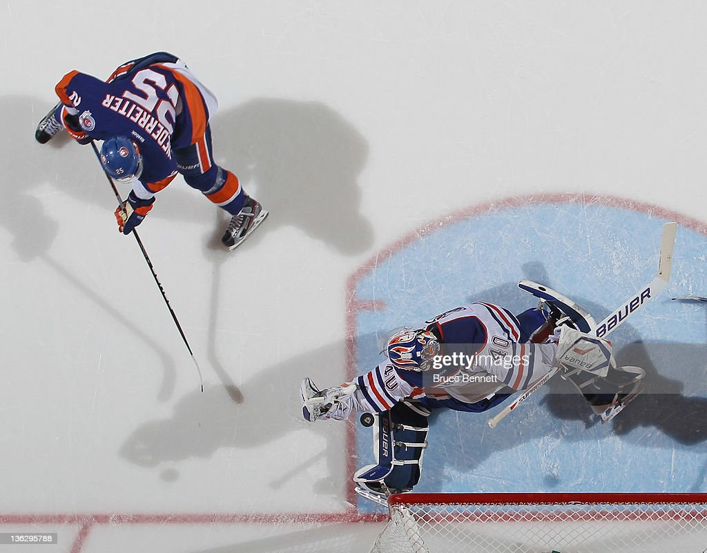 Devan Dubnyk #40 of the Edmonton Oilers makes the save on Nino Niederreiter #25 of the New York Islanders at the Nassau Veterans Memorial Coliseum on December 31, 2011 in Uniondale, New York. The Islanders defeated the Oilers 4-1.