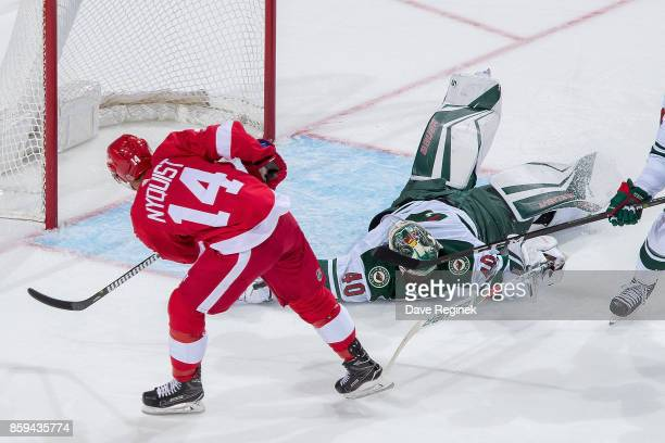 Devan Dubnyk of the Minnesota Wild makes a rolling back hand save on Gustav Nyquist of the Detroit Red Wings during the first ever NHL game at the...