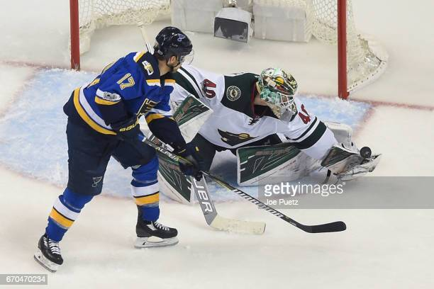 Devan Dubnyk of the Minnesota Wild makes a save as Jaden Schwartz of the St Louis Blues eyes the puck in Game Four of the Western Conference First...