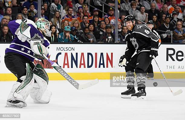 Devan Dubnyk of the Minnesota Wild plays the puck forward past Joe Pavelski of the San Jose Sharks during the Central Division AllStars and Pacific...