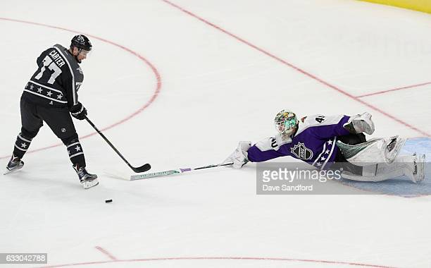 Devan Dubnyk of the Minnesota Wild tries for the poke check as Jeff Carter of the Los Angeles Kings backhands a drop pass for Joe Pavelski of the San...