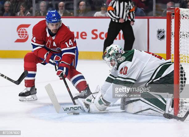 Devan Dubnyk of the Minnesota Wild tries to cover up the puck under pressure from Tomas Plekanec of the Montreal Canadiens in the NHL game at the...