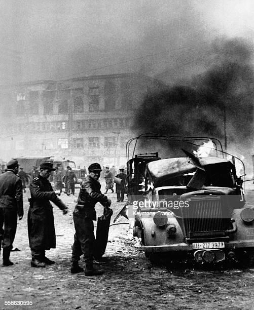 Devant la gare d'Anhalter tout est décombre une voiture de la WaffenSS brûle et les soldats essaient d'éteindre l'incendie à Berlin Allemagne en 1945