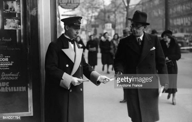 Devant l'entrée d'un cinéma un ouvreur distribue le programme des films à l'affiche à Paris France en décembre 1932