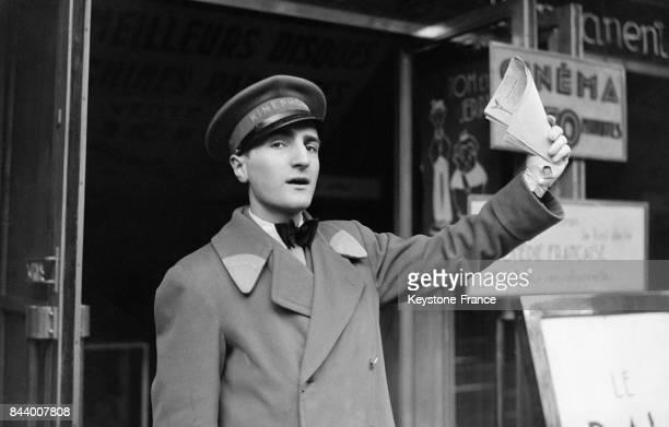 Devant l'entrée d'un cinéma un ouvreur à la crié appelle les Parisiens à venir voir un film à Paris France en décembre 1932