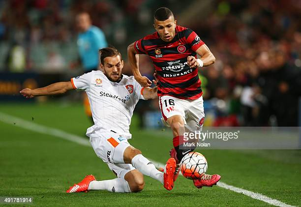 Devante Clut of the Roar and Mark Bridge of the Wanderers contest possession during the round one ALeague match between the Western Sydney Wanderers...