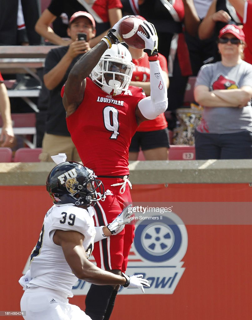 DeVante Parker #9 of the Louisville Cardinals makes a touchdown catch over top Sam Miller #39 of Florida International Panthers during their game at Papa John's Cardinal Stadium on September 21, 2013 in Louisville, Kentucky.