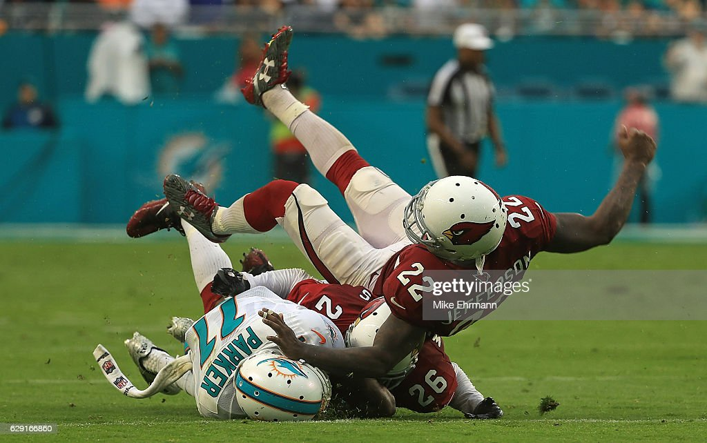 DeVante Parker #11 of the Miami Dolphins is tackled by Brandon Williams #26 and Tony Jefferson #22 of the Arizona Cardinals during a game at Hard Rock Stadium on December 11, 2016 in Miami Gardens, Florida.