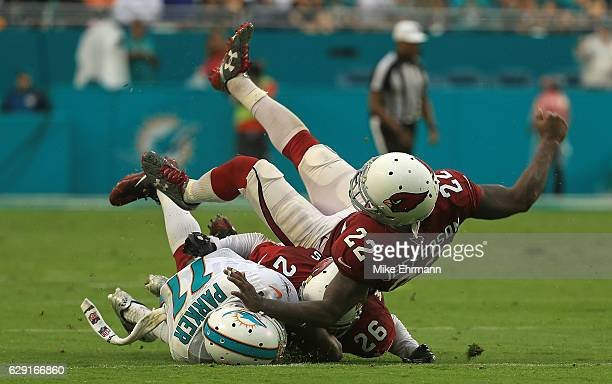DeVante Parker of the Miami Dolphins is tackled by Brandon Williams and Tony Jefferson of the Arizona Cardinals during a game at Hard Rock Stadium on...