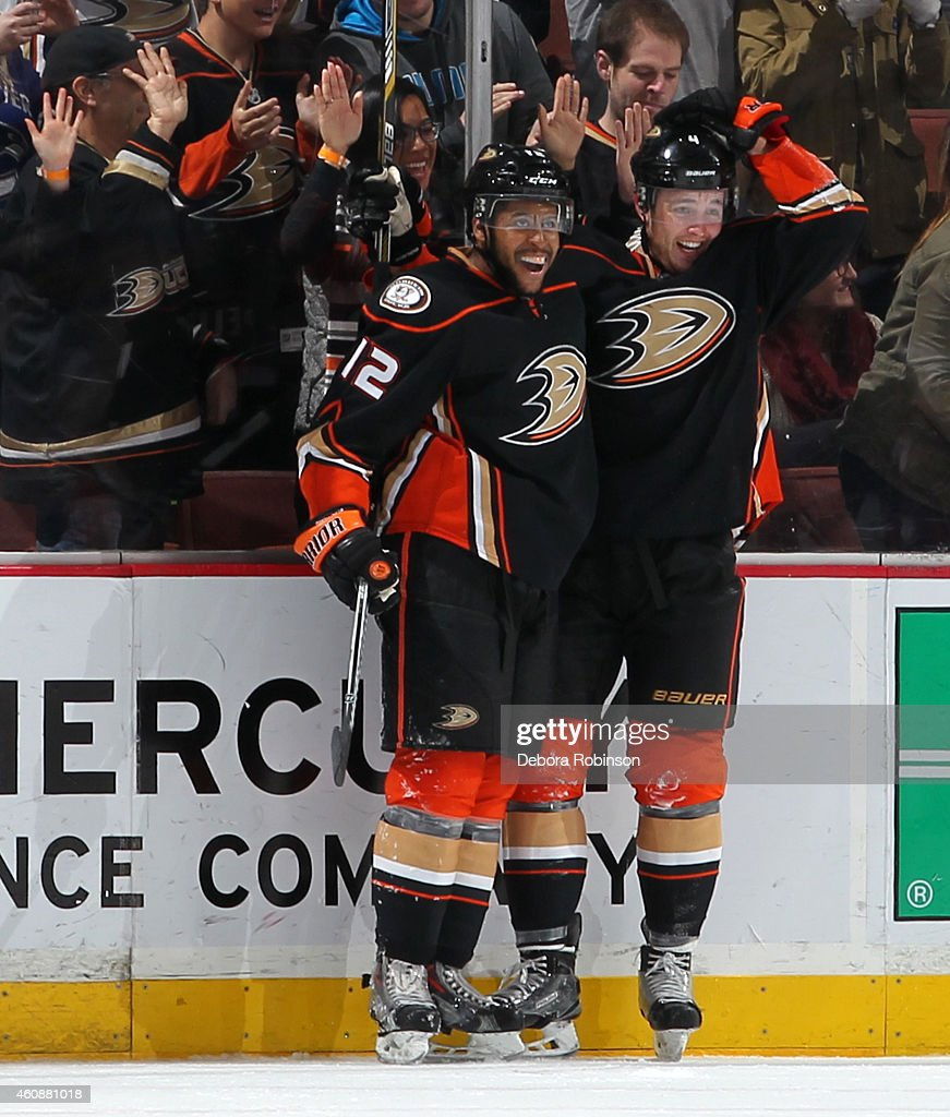 Devante Smith-Pelly #12 and Cam Fowler #4 of the Anaheim Ducks celebrate Fowler's overtime goal to win the game, 2-1, against the Vancouver Canucks on December 28, 2014 at Honda Center in Anaheim, California.