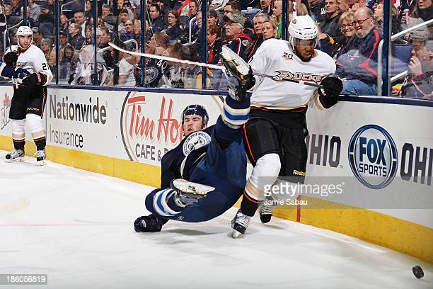 Devante SmithPelly of the Anaheim Ducks attempts to gain possession of the puck as David Savard of the Columbus Blue Jackets falls to the ice during...
