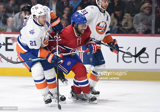 Devante SmithPelly of the Montreal Canadiens and Kyle Okposo of the New York Islanders battle for position in the NHL game at the Bell Centre on...