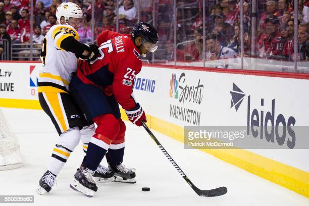 Devante SmithPelly of the Washington Capitals and Jake Guentzel of the Pittsburgh Penguins battle for the puck in the first period at Capital One...