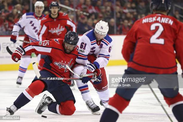Devante SmithPelly of the Washington Capitals and Rick Nash of the New York Rangers battle for the puck during the third period at Capital One Arena...
