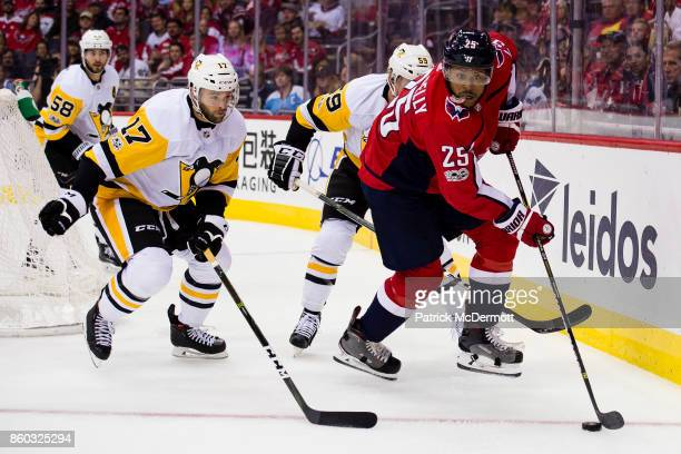 Devante SmithPelly of the Washington Capitals controls the puck against Jake Guentzel and Bryan Rust of the Pittsburgh Penguins in the first period...