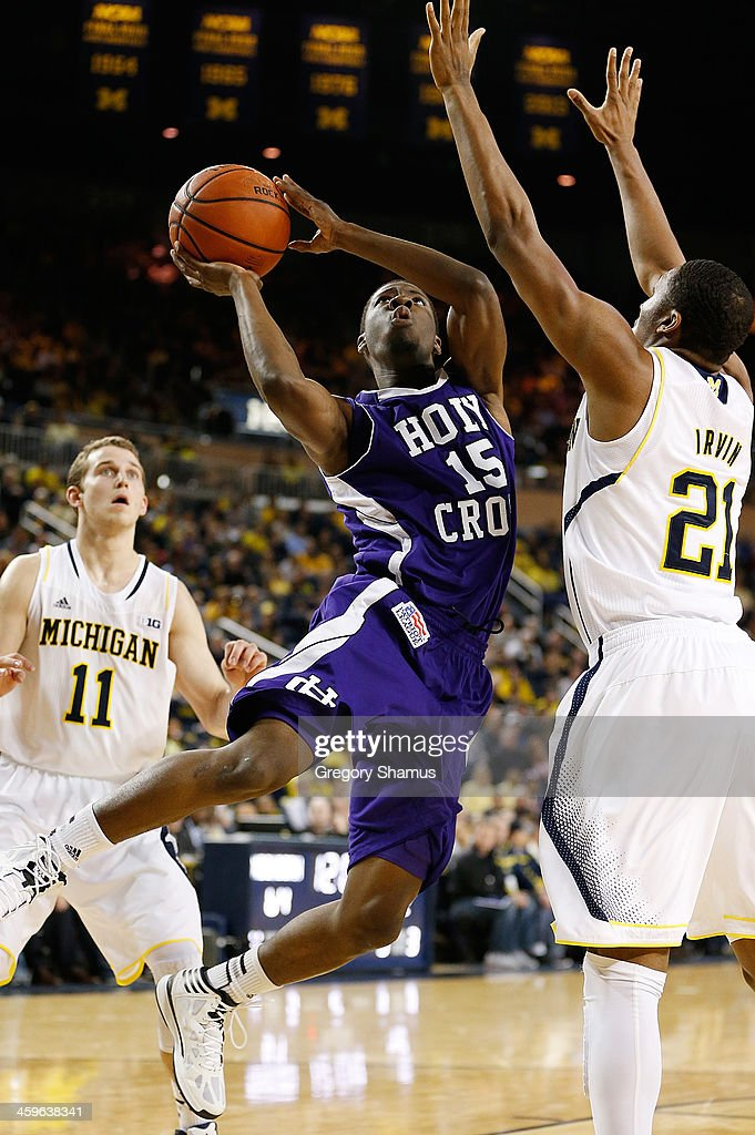 De'Vaughn Reid #15 of the Holy Cross Crusaders tries to get a second-half shot off against Zak Irvin #21 of the Michigan Wolverines at Crisler Center on December 28, 2013 in Ann Arbor, Michigan. Michigan won the game 88-66.