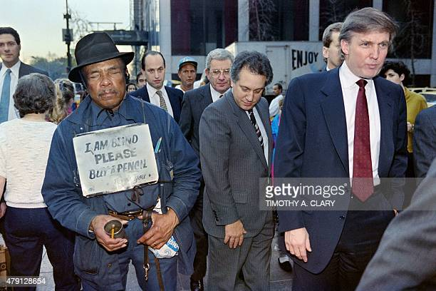 US developer Donald Trump walks down Fifth Avenue past a beggar after holding a news conference on November 16 1990 Trump announced he had reached a...